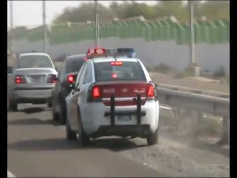 A Abu Dhabi police car pulls over a Speeder on Interstate 11 - Abu Dhabi towards Dubai. Abu Dhabi, United Arab Emirates, 2/20/2012.