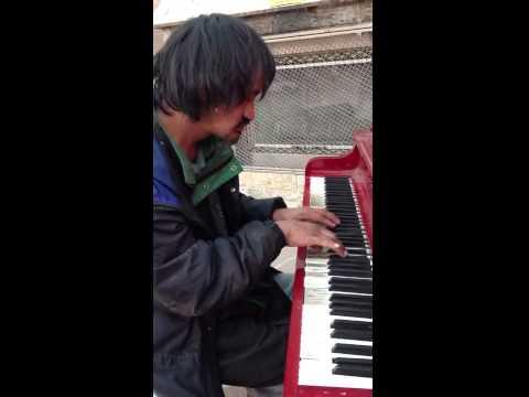 Парень с улицы играет свою музыку на пианино