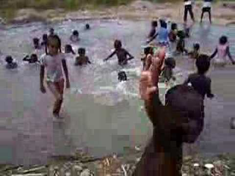 Haitian Refugees in the DR playing in the river - Back flip