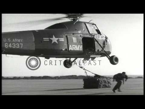 A US Army Sikorsky H-34 helicopter lifts off with a pallet of supplies from an ai...HD Stock Footage