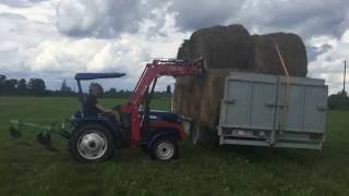 Loading hay bales on to truck with foton tractor