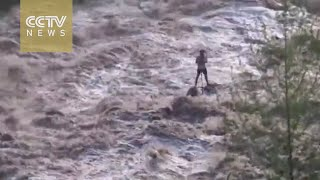 Man stranded in middle of turbulent flood