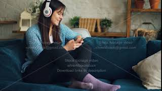 Pretty girl student is listening to music with headphones and touching smartphone screen having fun