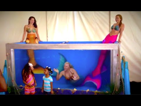 Professional Mermaid Performers in their traveling tank display