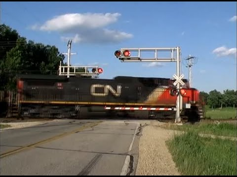 CN 2593 and CN 2541 pull an auto rack train south, down the Waukesha Subdivision. The MP 64.5 defect detector gives a readout at the end. This was filmed at ...