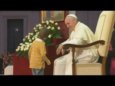 Young boy invades Vatican stage and hugs Pope Francis