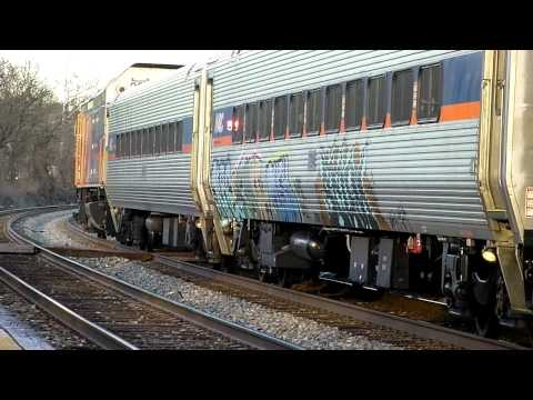 A MARC train with a passenger car with graffiti stops and then heads north at Muirkik.