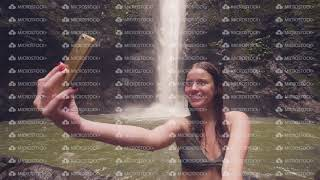 Young woman travel blogger doing selfie photo to mobile phone on mountain waterfall background
