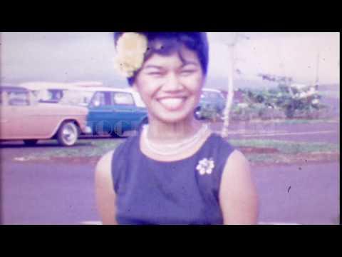 1964: Beehive hairdo happy Asian woman smiles flower in hair. KONA, HAWAII