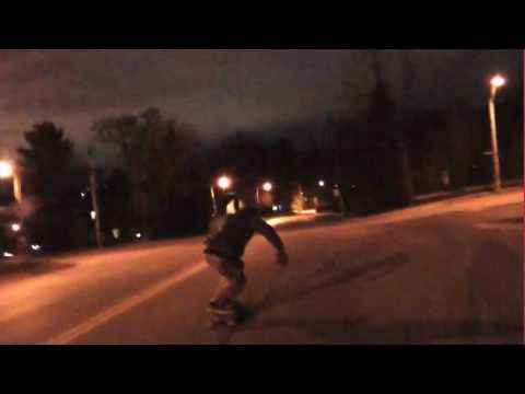 Downhill Skateboarder Hits Street Light