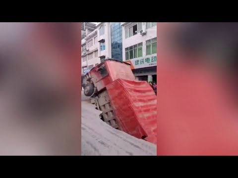 Truck falls into huge sinkhole that opened up on road in central China
