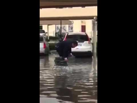 洪水で水浸しの路上で買い物カートに乗る男。どうしても濡れたくないんだもんw