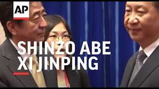 Japan's Prime Minister Shinzo Abe and Chinese President Xi Jinping hold a frosty handshake at APEC s