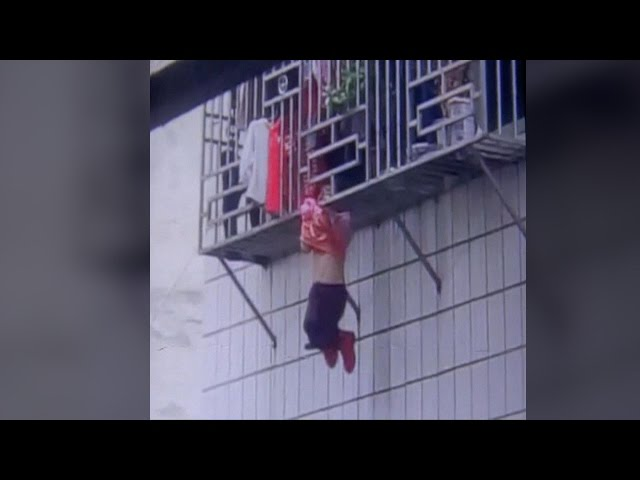 Two men save girl hanging by neck from fourth-story window