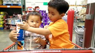 Brothers sharing drinks at Costco