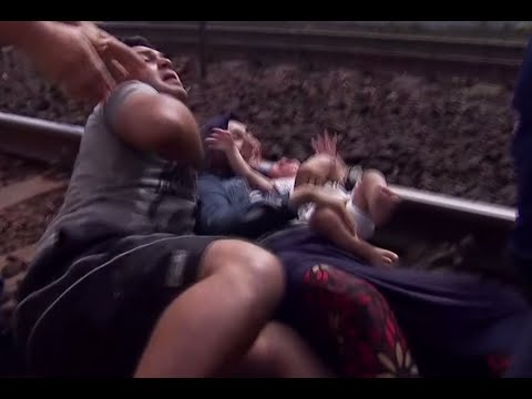 Desperate refugee pushes wife & kid on rail tracks as police hustle asylum seekers off train