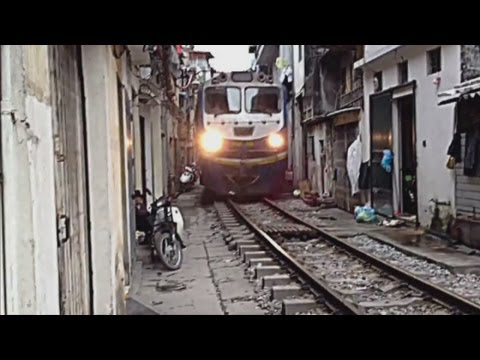 Train travels through narrow gap inbetween houses in Vietnam