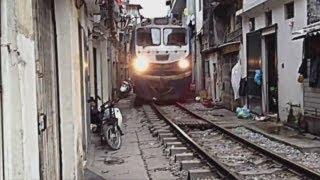 Train travels through narrow gap inbetween houses in Vietnam