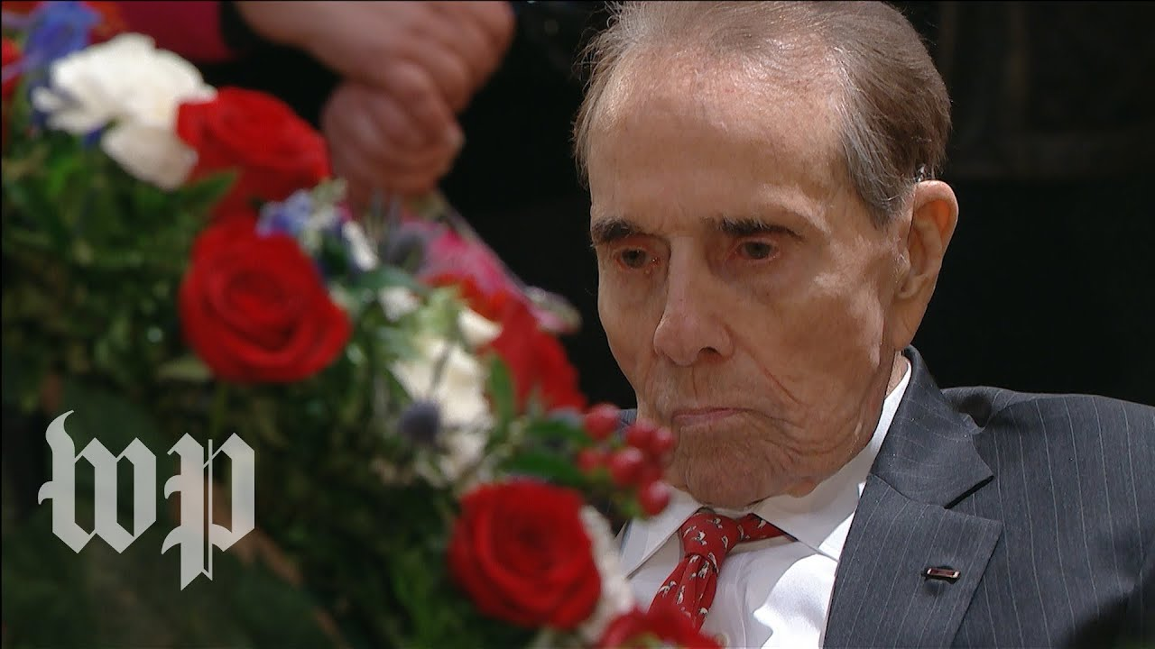 Bob Dole stands to pay respect to George H.W. Bush