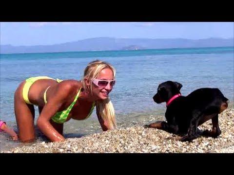 Doberman Puppy vs. Blonde Fitness Girl - Kölyök doberman játszik a tengerparton