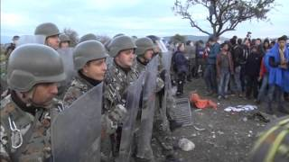 Stranded migrants try to storm into Macedonia, tear down fence.