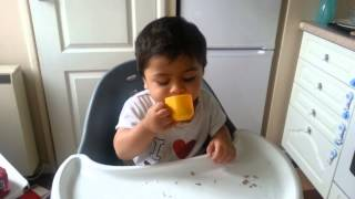 Baby Nirvan drinking milk from playset cup