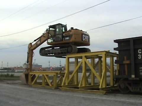 Watch Cat 319D LN climbing onto rail car