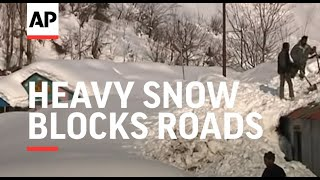Heavy snow blocks roads and burries homes in disputed region