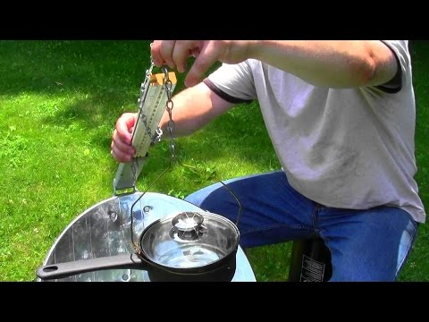 Satellite dish solar cooker - cooking a hamburger.