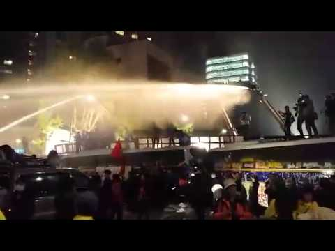 Riot police spray South Korean protestors with water cannons mixed with pepper spray powder.