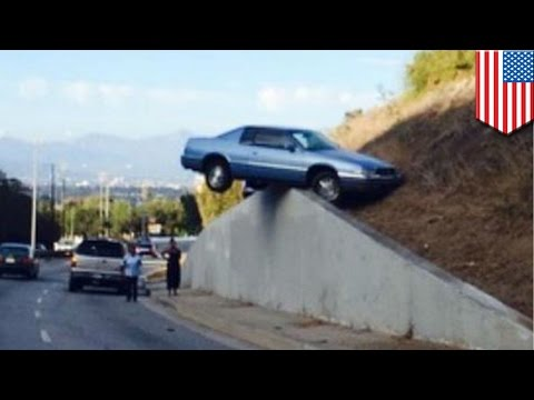 Crazy Los Angeles car accident sees vehicle lose control and land hanging off a wall