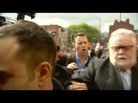 Rev Paul Flowers battles through the media pack as he leaves court