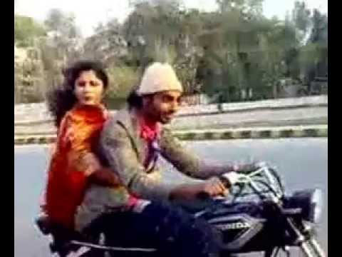 Pakistani man performing one wheeling with a girl sitting on bike.