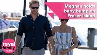 Meghan holds baby bump while walking hand in hand with Prince Harry on Fraser Island