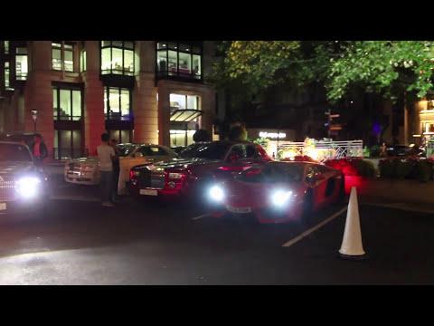 Orange Lamborghini drives off parking and revving on Park Lane in London, UK