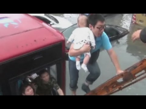 A baby is rescued from a trapped bus on a flooded road in east China
