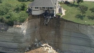Couple looks on as house falls off cliff