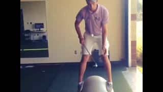 Guy hits Golf Ball while Standing on A Yoga Ball