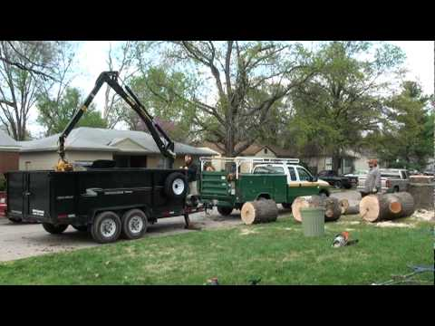 Loading a large sweet gum tree trunk with a grapple boom ...