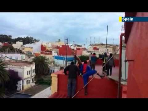 Desperate African illegal immigrants jump desert border fence to enter Spanish enclave Melilla