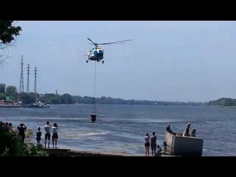 Новая Каховка вертолет делает забор воды для тушения пожара за котельней