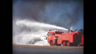 O-11A fire rescue truck douses a flaming airframe.