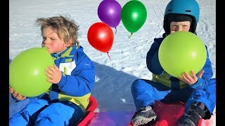 Balloon fun sledding challenge can we pop it?? Kids playing in the snow!!