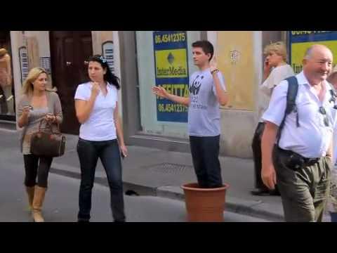 Joven imita una planta en una calle de Roma