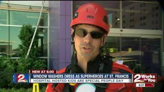 Window washers dressed as superheroes work at Saint Francis Children's Hospital