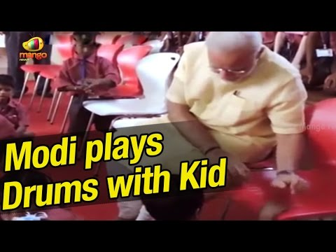 PM Modi plays drums with school kid at Education City in Chhattisgarh