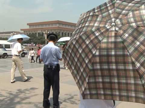 Police use umbrellas to stop filming on Tiananmen