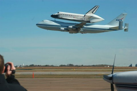 Shuttle Endeavour atop a modified 747 on low approach at Ellington Field near the NASA Johnson Space Center in Houston TX on Dec. 11 2008. The supporting C17...