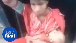 Mother sits in between moving train carriages whilst holding baby