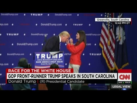 Woman inspects Donald Trump's hair on stage